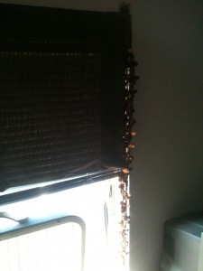 Closeup of a pillowcase and a scarf with shiny ovals being used as curtains above and next to a fan in a window.