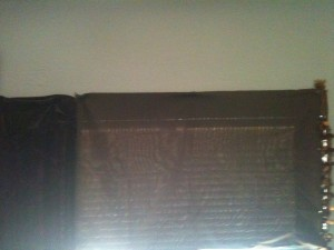 Partial image of pillowcase and scarf and shawl used as short curtains over the fan.